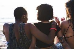 Groupe de femmes diverses s'asseyant à la plage ensemble Photos stock