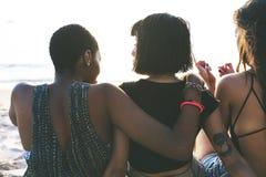 Groupe de femmes diverses s'asseyant à la plage ensemble Photos libres de droits
