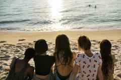 Groupe de femmes diverses s'asseyant à la plage ensemble Image libre de droits