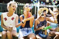 Groupe de femmes diverses s'asseyant par la bulle de savon de coup de piscine Photos stock