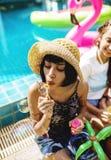 Groupe de femmes diverses s'asseyant par la bulle de savon de coup de piscine Photo libre de droits