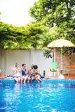 Groupe de femmes diverses s'asseyant par la piscine Photos stock