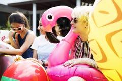 Groupe de femmes diverses s'asseyant par la piscine avec les tubes gonflables Photo libre de droits