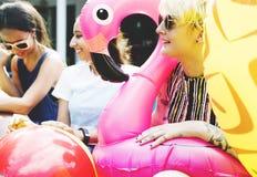 Groupe de femmes diverses s'asseyant par la piscine avec les tubes gonflables Images stock