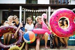 Groupe de femmes diverses s'asseyant par la piscine avec les tubes gonflables Photos libres de droits
