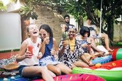 Groupe de femmes diverses s'asseyant par la piscine avec les tubes gonflables Photographie stock libre de droits
