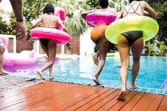 Groupe de femmes diverses sautant à la piscine avec le tube gonflable Images libres de droits