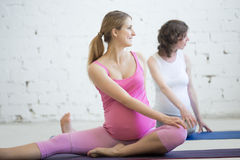 Groupe de femmes enceintes faisant le yoga prénatal Torsion spinale en janvier Image stock