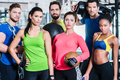 Groupe de femmes et d'hommes dans le gymnase posant à la formation de forme physique photographie stock