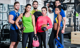 Groupe de femmes et d'hommes dans le gymnase posant à la formation de forme physique image stock