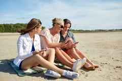 Groupe de femmes heureuses avec des smartphones sur la plage Images libres de droits