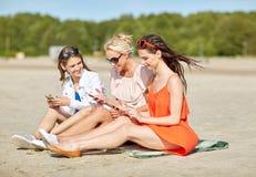 Groupe de femmes heureuses avec des smartphones sur la plage Images stock