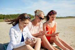 Groupe de femmes heureuses avec des smartphones sur la plage Photographie stock