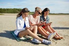 Groupe de femmes heureuses avec des smartphones sur la plage Photos libres de droits