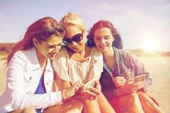 Groupe de femmes heureuses avec des smartphones sur la plage Photo libre de droits