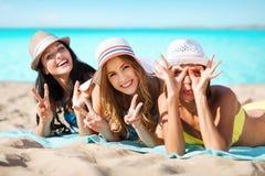 Groupe de femmes heureuses dans des chapeaux prenant un bain de soleil sur la plage Images stock