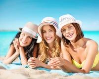 Groupe de femmes heureuses dans des chapeaux prenant un bain de soleil sur la plage Photographie stock