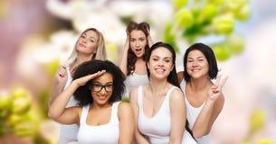 Groupe de femmes heureuses dans les sous-vêtements blancs ayant l'amusement Image libre de droits