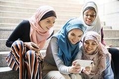 Groupe de femmes islamiques regardant le smartphone Image stock