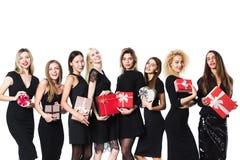 Groupe de femmes de mode dans la robe noire avec des cadeaux dans des mains d'isolement photographie stock libre de droits