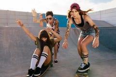 Groupe de femmes montant des planches à roulettes au parc de patin Photos stock