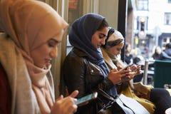 Groupe de femmes musulmanes britanniques textotant en dehors du café photos stock
