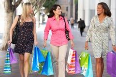 Groupe de femmes portant des sacs à provisions sur la rue de ville Photo libre de droits