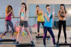 Groupe de femmes posant sur de pas aérobie Image stock