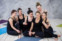 Groupe de femmes s'asseyant et détendant après une longue classe de yoga et prenant le selfie Photos stock