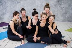 Groupe de femmes s'asseyant et détendant après une longue classe de yoga et prenant le selfie Image stock