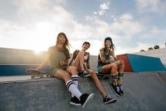 Groupe de femmes s'asseyant sur la rampe en parc de patin Image libre de droits