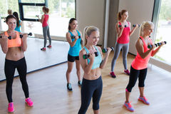 Groupe de femmes s'exerçant avec des haltères dans le gymnase Photo stock