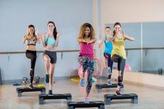 Groupe de femmes s'exerçant sur de pas aérobie Photo stock