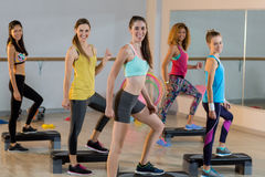Groupe de femmes s'exerçant sur de pas aérobie Photographie stock