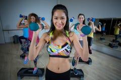 Groupe de femmes s'exerçant sur de pas aérobie Image stock