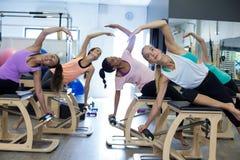 Groupe de femmes s'exerçant sur la chaise de wunda Image libre de droits