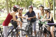 Groupe de femmes se reposant pendant le tour de cycle par le parc Images stock