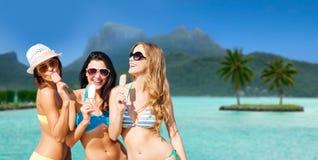 Groupe de femmes de sourire mangeant la crème glacée sur la plage Photo libre de droits