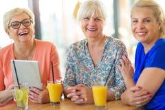 Groupe de femmes supérieures à l'aide du comprimé dans une barre Images stock