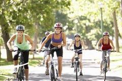 Groupe de femmes sur le tour de cycle par le parc photos libres de droits