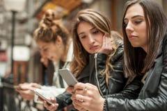 Groupe de filles à l'aide des téléphones portables Isolement et emotio de technologie Image stock