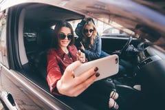 Groupe de filles ayant l'amusement avec la voiture Prise du selfie tout en conduisant dans le voyage Images stock