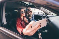 Groupe de filles ayant l'amusement avec la voiture Prise du selfie tout en conduisant dans le voyage Image stock
