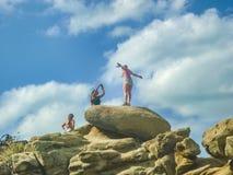 Groupe de filles ayant l'amusement en haut d'une roche Image libre de droits