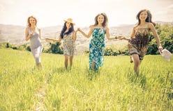 Groupe de filles courant dans un domaine Photographie stock libre de droits