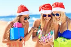 Groupe de filles dans des chapeaux de Santa ayant l'amusement sur la plage Photographie stock libre de droits