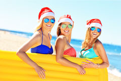 Groupe de filles dans des chapeaux de Santa ayant l'amusement sur la plage Photographie stock