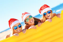 Groupe de filles dans des chapeaux de Santa ayant l'amusement sur la plage Photo stock