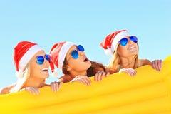 Groupe de filles dans des chapeaux de Santa ayant l'amusement sur la plage Images libres de droits