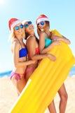 Groupe de filles dans des chapeaux de Santa ayant l'amusement sur la plage Photos libres de droits